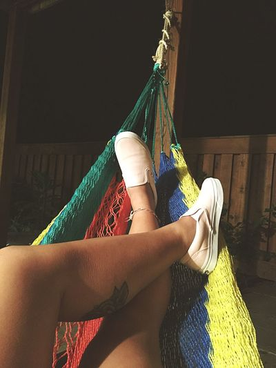 Low section of woman relaxing in hammock at night