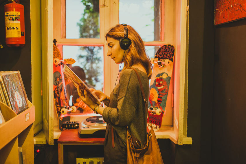 a girl listening to music in the vintage vinyl store Listening Listening To Music Music Vinyl Woman Female Girl Lifestyles Old Vintage Vintage Vinyl Vinyl Store