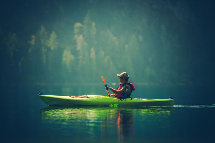 Side view of man kayaking in lake