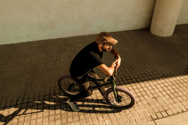 Young man riding bicycle on footpath against wall