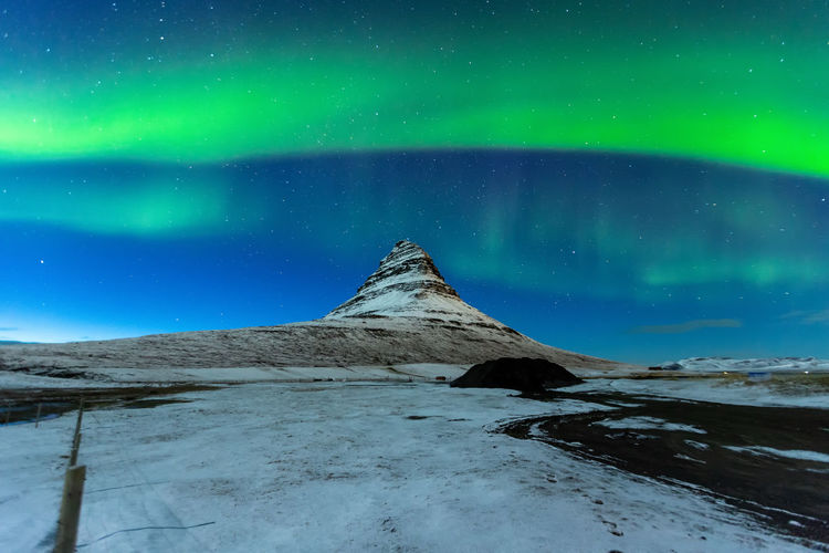 Aurora Borealis or northern light above kirkjufell mountain in iceland Aurora Borealis Iceland Kirkjufell Astronomy Aurora Polaris Beauty In Nature Cold Temperature Environment Idyllic Landscape Mountain Nature Night No People Scenics - Nature Sky Snow Snowcapped Mountain Space Star - Space Tranquil Scene Tranquility Winter