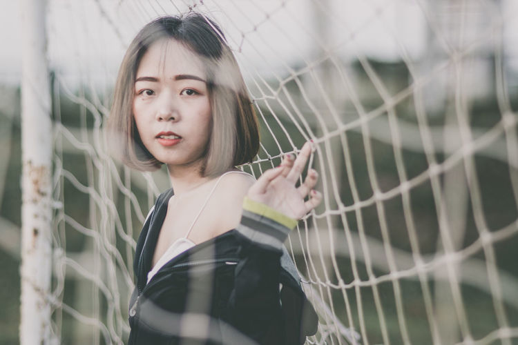 Portrait of beautiful young woman standing at goal