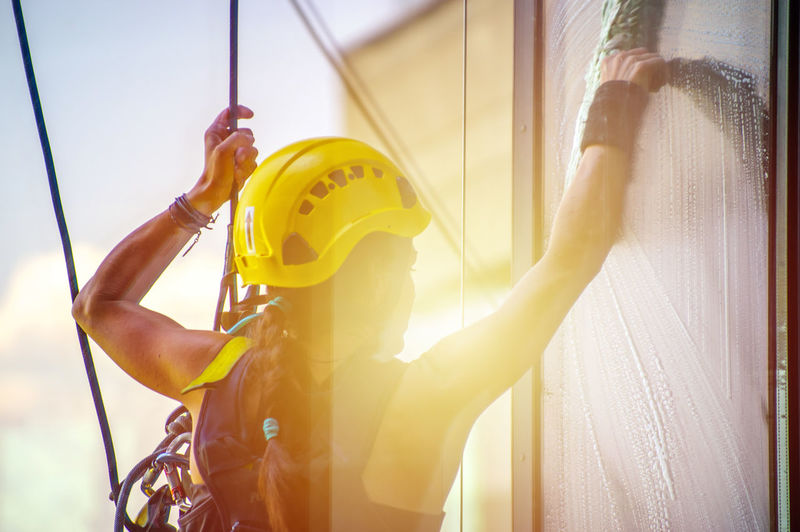 Cleaner Cleaning Washing Woman Activity Alpinism Alpinist Day Headwear Helmet Holding Job Leisure Activity Lifestyles Nature Occupation One Person Outdoors Real People Ropes Safety Sport Sunlight Window Yellow