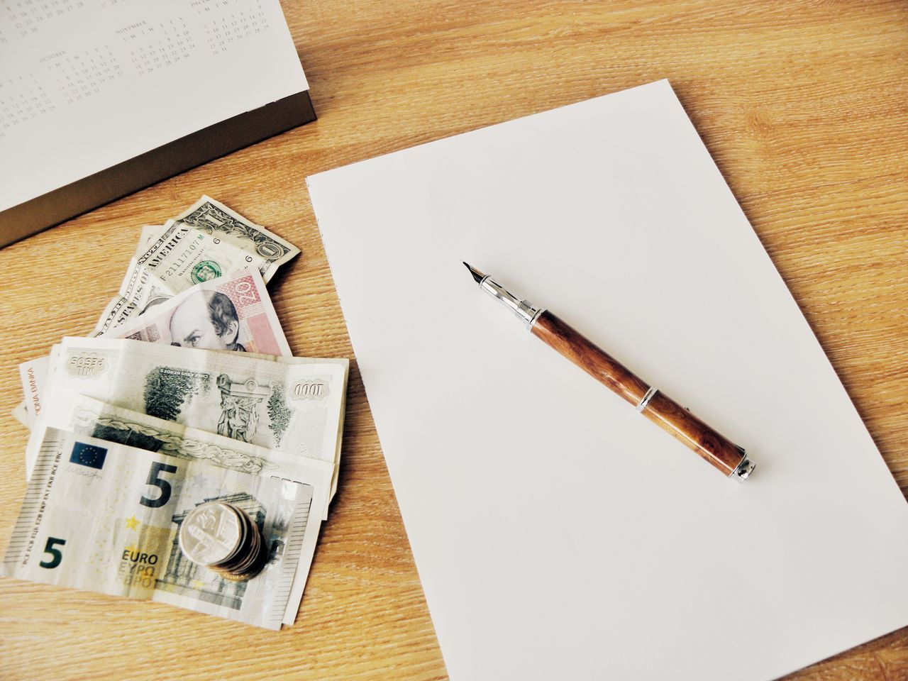 High Angle View Of Pen On Table With Currency