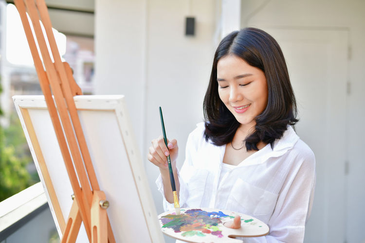 Young woman holding colorful palate by canvas