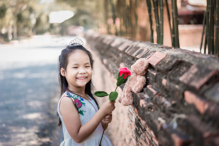 Portrait of cute girl smiling while standing on plant