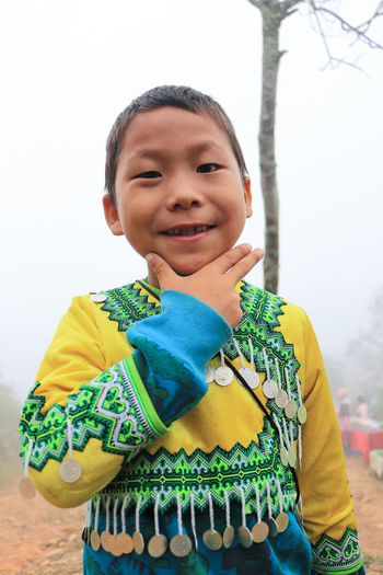 Portrait of smiling boy in traditional clothing standing against sky