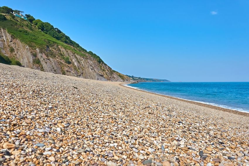 Beach Beauty In Nature Blue Clear Sky Day Gravel Horizon Over Water Land Mountain Nature No People Outdoors Pebble Rock Scenics - Nature Sea Sky Solid Stone Tranquil Scene Tranquility Water