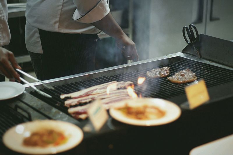 Midsection of chefs grilling beef meat on barbecue grill