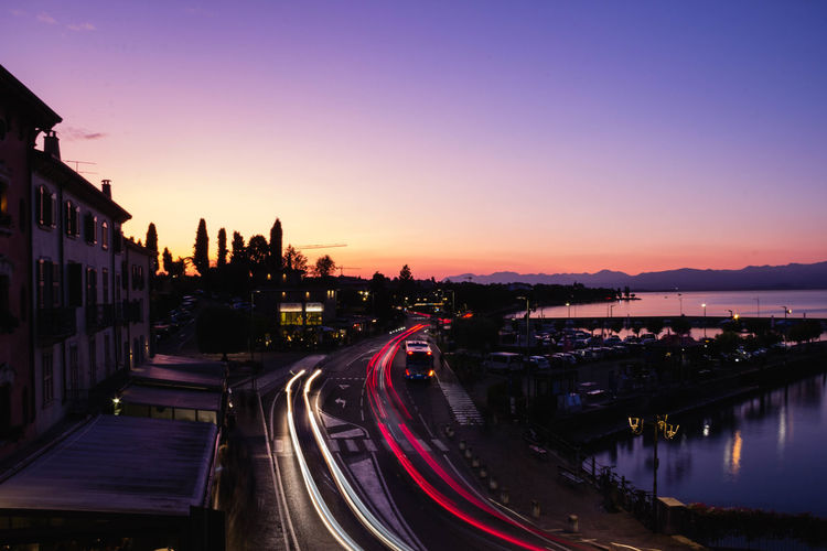 High angle view of illuminated city at sunset