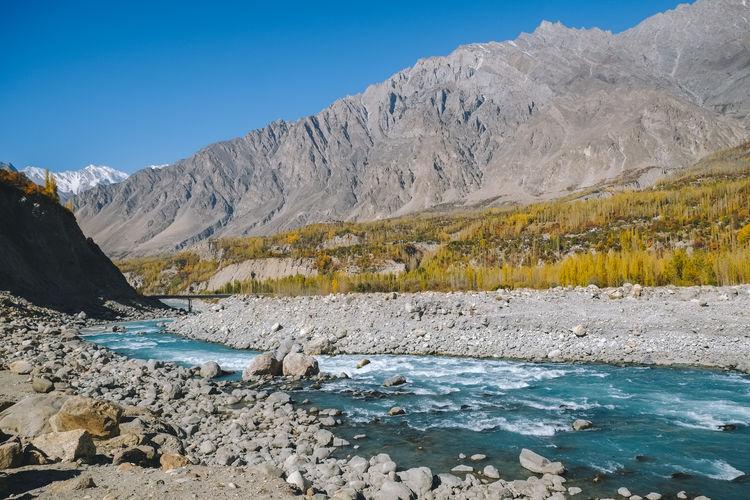 Colorful hunza nagar valley in autumn. forest and river against karakoram mountain range, pakistan.