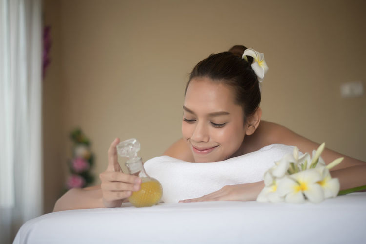 Smiling young woman with oil lying on massage table in spa