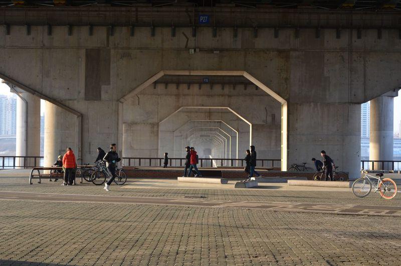 People walking under bridge in city