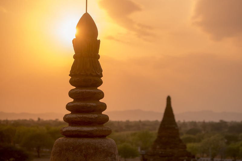 Steeple of historic temple against sky during sunset