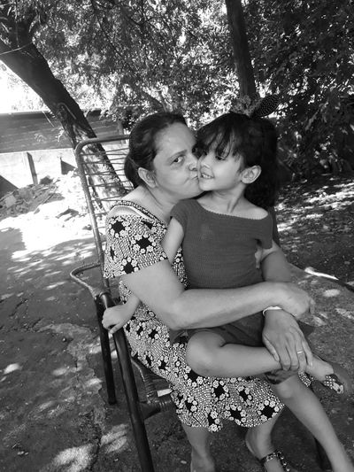 Portrait of mother kissing daughter while sitting on chair against trees