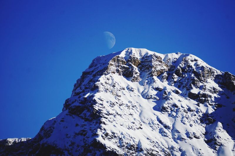 Mountain Peak with Moon Graubünden Switzerland Arosa Half Moon Blue Sky Mountain Beauty In Nature Winter Snow Cold Temperature Scenics - Nature Clear Sky Nature Tranquil Scene Tranquility Low Angle View Snowcapped Mountain No People Day Rock Formation Rock Mountain Range Mountain Peak My Best Photo The Great Outdoors - 2019 EyeEm Awards