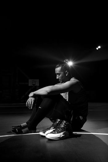 Portrait of Basketball player with Basketball shoes After The Game  Basketball Basketball Court Black & White Black And White Casual Clothing Dark Flash Light Jordan Loneliness Man Night Photography Night Portrait Person Portrait Portrait Of Player Relaxation Rest Shoe Shoes Off Side View Sitting Sitting Thinking Young Adult