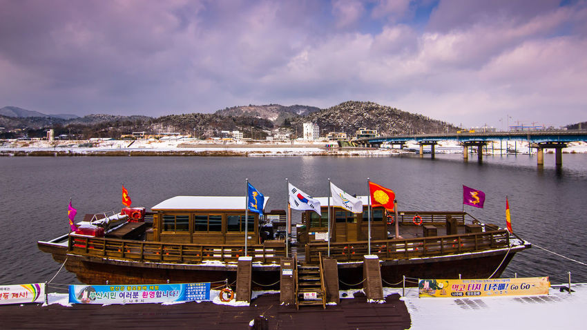 this Snowfall and boat photo was taken at Yansang river Naju, South Korea Cloud EyeemNaju EyeemSouthKorea Architecture Beauty In Nature Building Exterior Built Structure Cloud - Sky Day Eyeemhere Flag Mode Of Transport Moored Mountain Nature Nautical Vessel No People Outdoors River Scenics Sea Sky Transportation Travel, Water