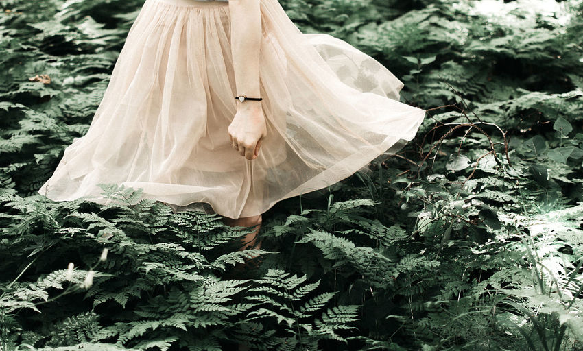 Midsection of woman standing amidst plants in forest