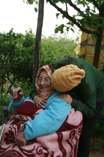Woman kissing smiling grandmother at yard