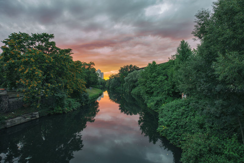 Scenic View Of River Amidst Trees Against Cloudy Sky During Sunset