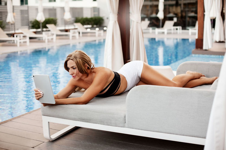 Sporty woman in a bikini sunbathes, relaxes and reads on a tablet while relaxing