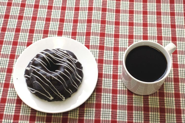 High Angle View Of Fresh Bundt Cake Served With Black Coffee On Table