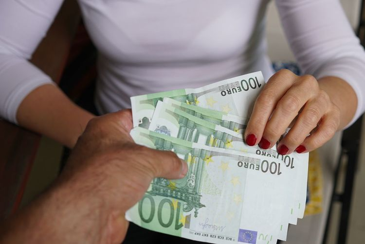 Midsection of businesswoman receiving money from man