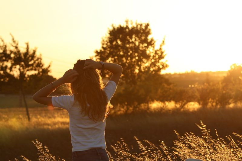 Rear view of woman standing on field during sunset