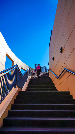 Climbing up a staircase Architecture Blue Built Structure Clear Sky Climbing Day Full Length Hand Rail Leisure Activity Lifestyles Low Angle View Men Outdoors Railing Real People Sky Staircase Stairs Standing Steps Steps And Staircases