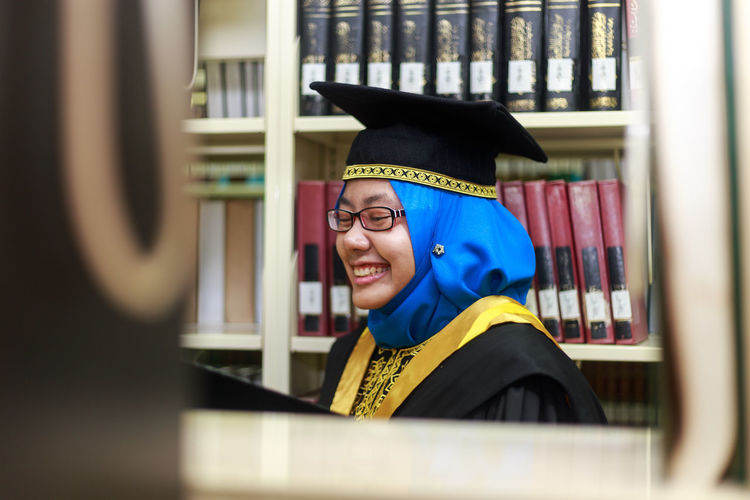 Young Woman Wearing Graduation Gown In Library