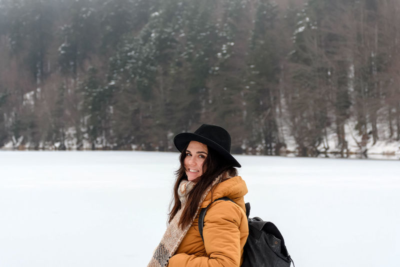 Portrait of a happy young woman standing by frozen lake. ice, snow, cold weather, hat.