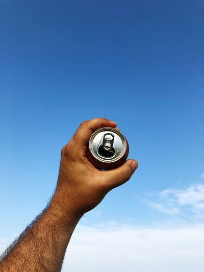 Low angle view of hands holding tin can against blue sky