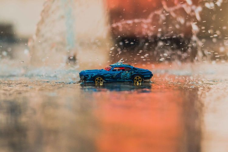 Toy car moving on puddle during rainy season