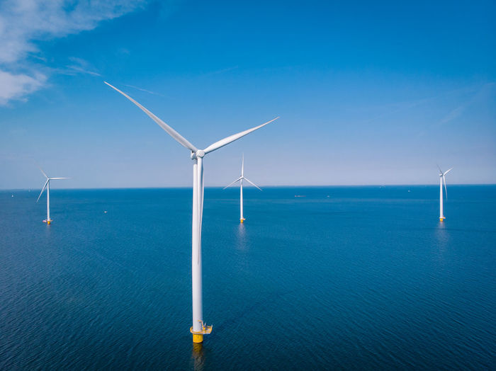 Wind turbines in sea against blue sky, windmills by sea against sky, windmills park westermeerdijk
