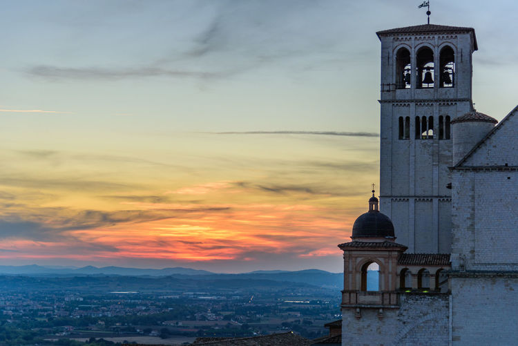 Basilica of san francisco amidst town against cloudy sky during sunset