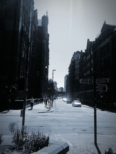 Sun Rays Sun Reflection On Windscreen Manchester City Centre Travel Destinations City Life City Buildings Contrast Perspective Blackandwhite Photography Multiple Buildings Clear Sky Architecture City Streets  City Street Post Directions Pedestrians High Contrast Image Shadows & Lights