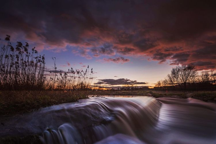 Flowing river stream in field against sky during sunset
