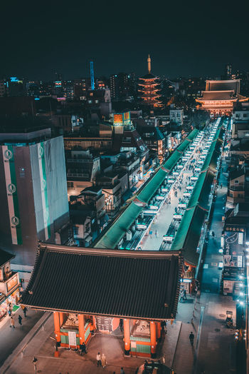 High angle view of illuminated buildings and street in city at night
