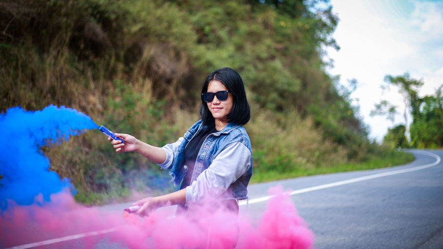 Portrait Of Young Woman Holding Distress Flare While Standing By Road
