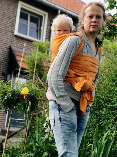 Portrait of woman carrying daughter while standing at yard
