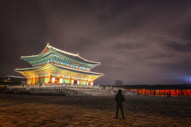 Gyeongbokgung Palace At Night In South Korea, with the name of the palace 'Gyeongbokgung' on a sign Gateway; Grounds; Kwanghwamun; Landmark; Old; Historical; Royal; Gate; City Architecture Beauty In Nature Building Exterior Built Structure Cloud - Sky Gyeongbokgung; Palace; Korea; Seoul; Night; South; Korean Illuminated Lightning Nature Night One Person Outdoors People Real People Sky Standing Tourism Travel Destinations