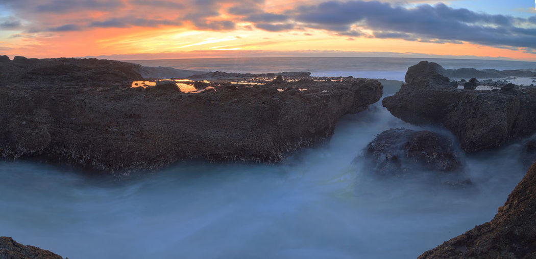 Water Flowing By Rock Formations At Little Corona Beach During Sunset