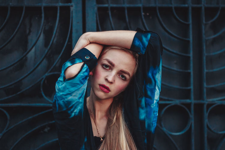 Portrait of beautiful young woman standing against metal gate