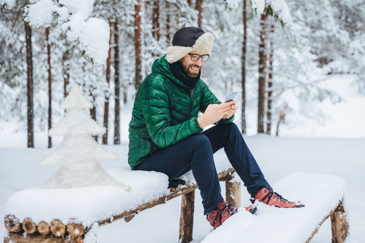 Man using mobile phone while sitting on snow