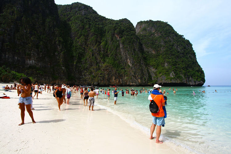 People on beach against mountain