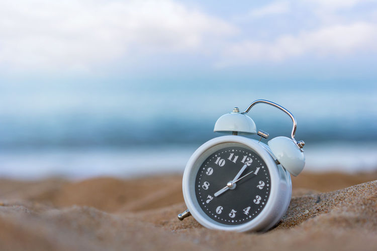 Close-up of clock on the beach