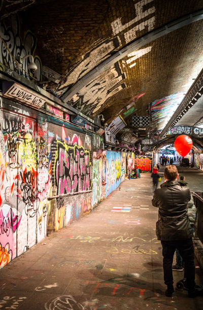 People wandering through the Leake Street tunnel surrounded by graffiti and street art. Graffiti Leake St Leake Street Tunnel Street Art/Graffiti Street Artist Adult Architecture Artist Day Graffiti Graffiti Art Graffiti Wall Men Multi Colored People Real People Street Street Art Street Art Photography Streetphotography Tunnel