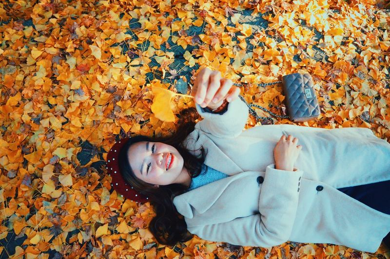 High angle view of woman lying down on autumn leaves