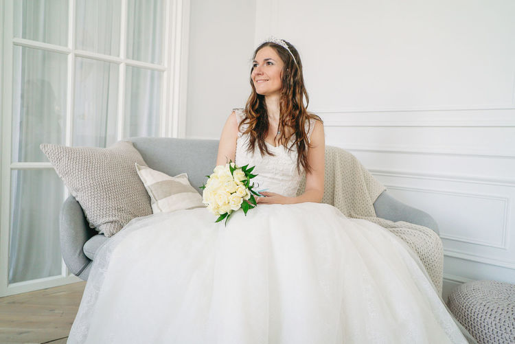 Beautiful smiling brunette woman bride in wedding dress with classical white roses bouquet in living room One Person Furniture Women Sitting Beautiful Woman Lifestyles Young Adult Long Hair White Color Adult Flower Indoors  Young Women Looking At Camera Beauty Hairstyle Portrait Three Quarter Length Hair Fashion Flower Arrangement Bouquet Contemplation